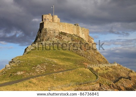 Lindisfarne castle on a sunlit afternoon in Autumn, Holy Island, United Kingdom - stock photo