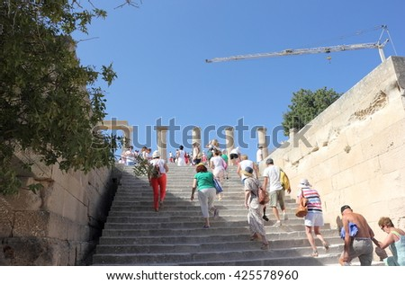 Lindos, Rhodes, Greece - September 09, 2015: Tourists at the top of Lindos ancient Acropolis ruins. - stock photo
