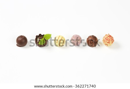 line of assorted belgian chocolate pralines on white background - stock photo