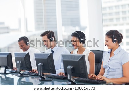 Line of call centre employees working on computers - stock photo