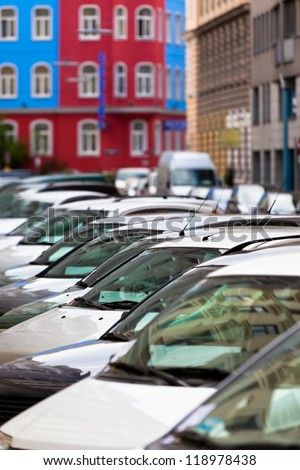 Line of Cars on the city street. Bright houses as a background - stock photo