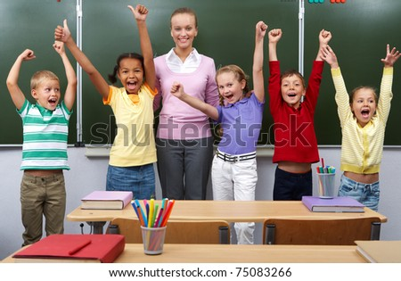 Line of cute schoolchildren raising arms with their teacher in the middle - stock photo