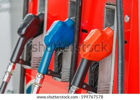 line of gasoline pump nozzles - stock photo