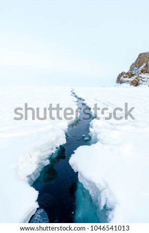 Line of ice cracks between ice sheet on Lake Baikal in Irkutsk, Russia on late winter. (Selective focus)