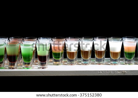 Line of many drinking small glasses with tasty alcoholic shooters shots cocktail drinks green red white and orange colored beverage standing on bar happy night party on black background, horizontal - stock photo