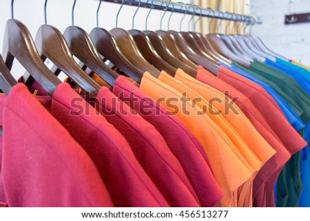 Line of multicolored clothes on wooden hangers in store. Sale