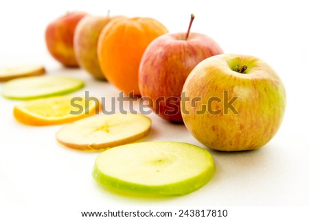 line of red and green apples and slices with one orange