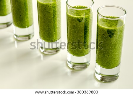 Line of shot glasses filled with fresh spinach and kale detox health smoothie - stock photo