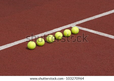 Line of six yellow tennis balls on court - stock photo