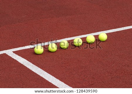 Line of six yellow tennis balls on red synthetic court - stock photo