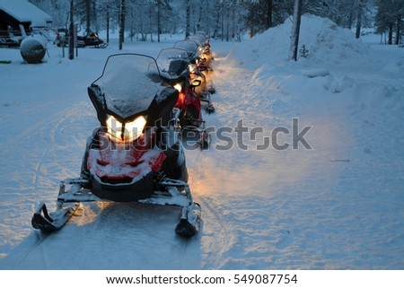 line of snowmobiles with their lights on