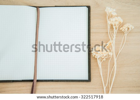 Line paper notebook open on wood texture background with dried flower decoration - stock photo
