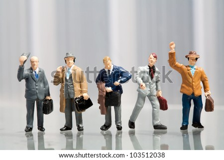 Line-up of tiny miniature figures of male office workers in varying attire on a reflective surface with copyspace
