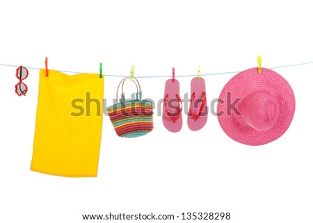 Line with hanging flip flops and pink straw summer hat towel and sunglasses - stock photo