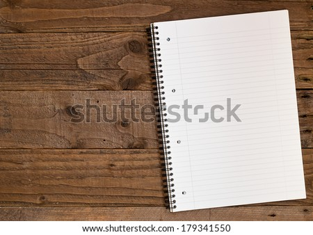 Lined A4 ring bound pad on a double page spread rustic wooden background in portrait orientation with copy space to the left for insertion of your message, photographs or design elements. - stock photo