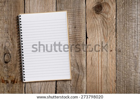 Lined notepad on old wooden background - stock photo