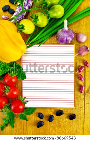 Lined sheet of paper small red and yellow tomatoes, yellow bell pepper, green onions, parsley, whole and two cloves garlic, black beans and kidney beans on a wooden board - stock photo