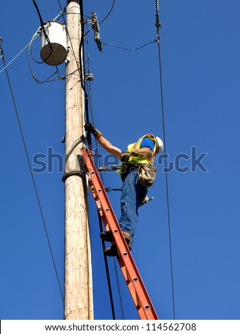 Lineman climbs utility pole to fix problem.  He is standing on a ladder wearing a helmet and safety belt.  Blue sky frames him. - stock photo