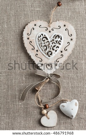 Linen background with christmas decoration. Wooden hearts. Wedding, xmas rough texture flat lay