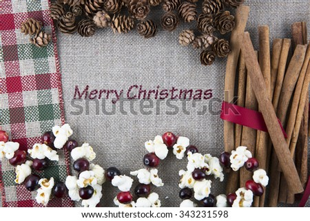 Linen fabric printed with Merry Christmas surrounded by cinnamon sticks, popcorn garland and pine cones. - stock photo