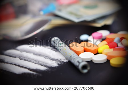 lines of cocaine beside a wrapped up dollar bill and narcotic pills - stock photo