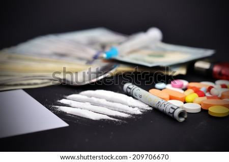 lines of heroin beside a wrapped up dollar bill and narcotic pills - stock photo