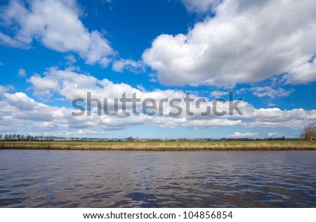 lines of land, water and blue sky with blue puffy clouds