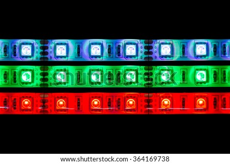 Lines of multicolored LED stripe lights on black background - stock photo