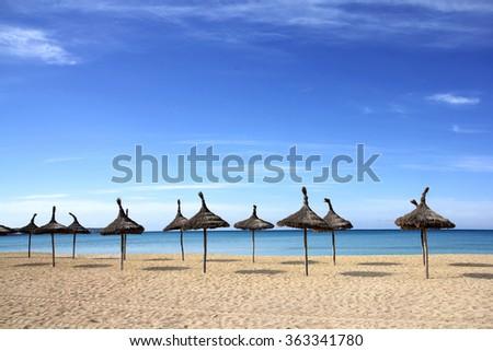 Lines of palm umbrellas on the beach - stock photo