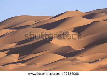 Lines of sand dunes on a hill near Liwa Oasis in the United Arab Emirates - stock photo