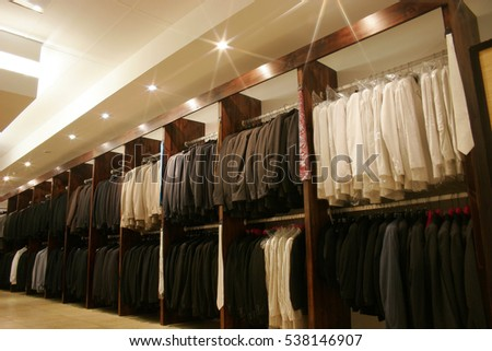 Lines of suits hanging in a clothing shop. Soft filter and starburst effect added.