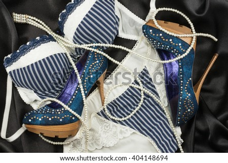 Lingerie, beads and shoes lying on black silk, top view - stock photo