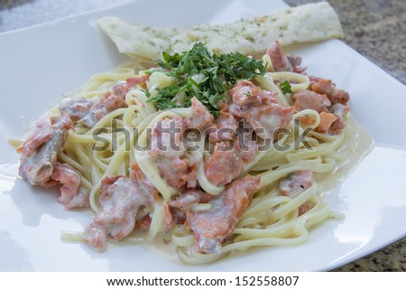 Linguine Pasta and Smoked Salmon Fish Cooked with  Alfredo Sauce Garnished with Parsley Closeup