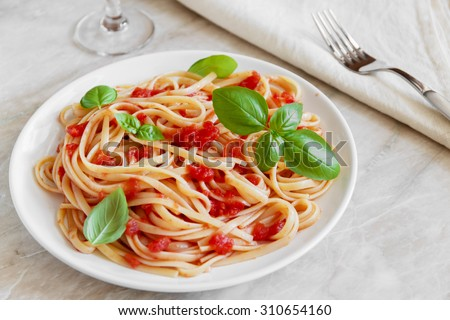 Linguine pasta in tomato sauce on a plate - stock photo