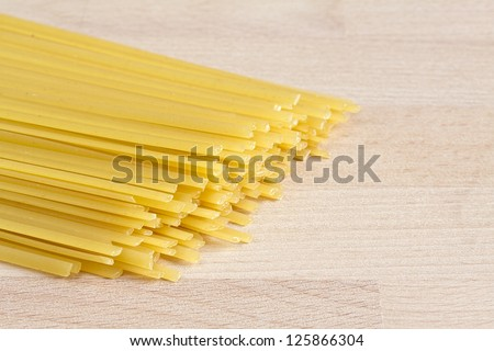 Linguine pasta on wooden board - stock photo