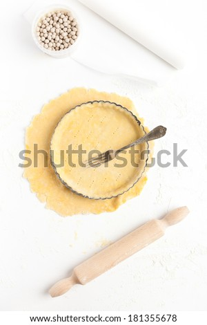Lining a fluted tart tin with shortcrust pastry dough, base pricked with a fork. Taken on a floured white surface, directly from above with rolling pin, ceramic baking beans and white parchment paper. - stock photo