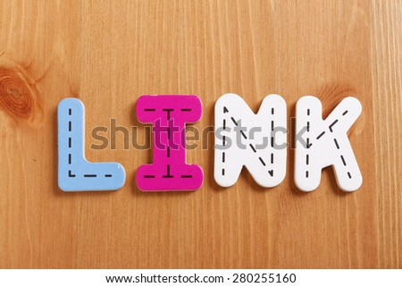 LINK, spell by woody puzzle letters with woody background - stock photo