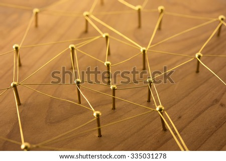 Linking entities. Network, networking, social media, internet communication abstract. Web of gold wires on rustic wood. - stock photo