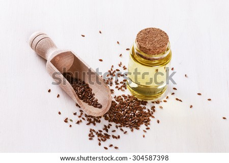 Linseed and bottled flaxseed oil over white wooden background - stock photo