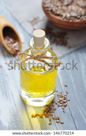 Linseed oil and flax seeds on wooden background - stock photo