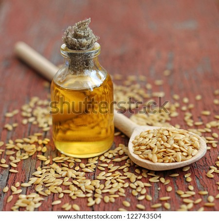 linseed oil in bottle on wooden background, close-up - stock photo