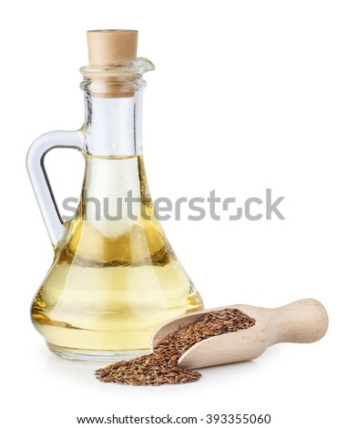 Linseed oil in glass bottle and flax seeds in wooden scoop isolated on white background - stock photo