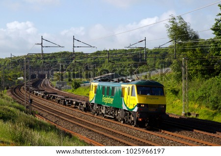 LINSLADE, UK - JUNE 3: A Freightliner operated class 90 loco hauled intermodal freight train heads back to its northern depot with a rake of empty flats on June 3, 2015 in Linslade