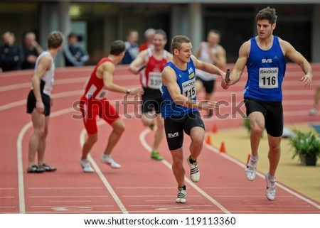 LINZ, AUSTRIA - FEBRUARY 25: Angel Somov (#116, Austria)  and his team place second in the men's 4x200m relay event in Linz, Austria on February 25, 2012. - stock photo