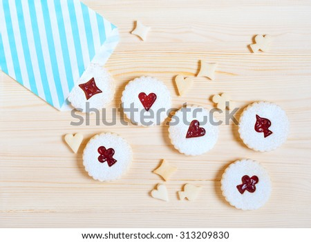 Linzer cookies with cherry jam on the wooden table