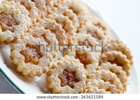 Linzer shortbread cookies with jam and decorated with powdered sugar on a white plate - stock photo