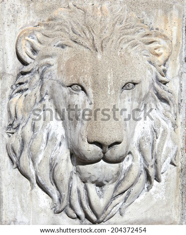 Lion face carved in stone on a wall outside.