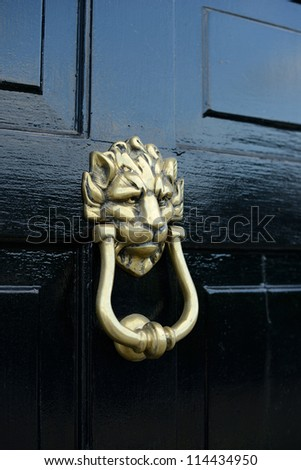 lion head door knocker on a black pained door - stock photo
