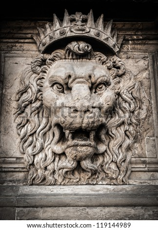 Lion head relief on the facade