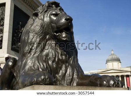 Lion in Trafalgar Square with National Portrait gallery in background - stock photo